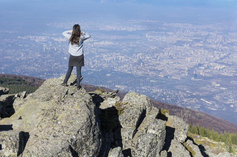 Mountaineer woman on top of a mountain looking the city view royalty free stock photography