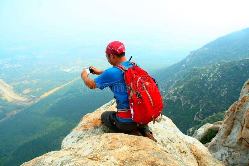 Mountaineering entuzjasta bierze telefon komórkowy fotografię przy falezy krawędzią Songshan ` s Shaolin halny szczyt zdjęcie royalty free