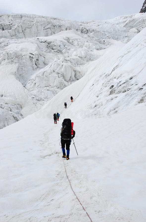 Mountaineers on the glacier. Group of mountaineers climbing up by glacier trail in high mountains stock photos