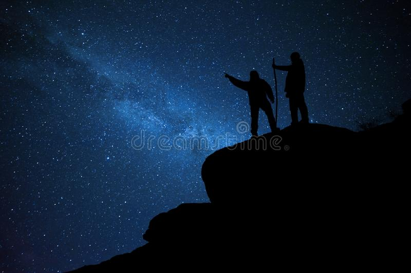 Mountaineers on rock enjoying view of night sky. With stars, hiking lifestyle, mans on top royalty free stock images