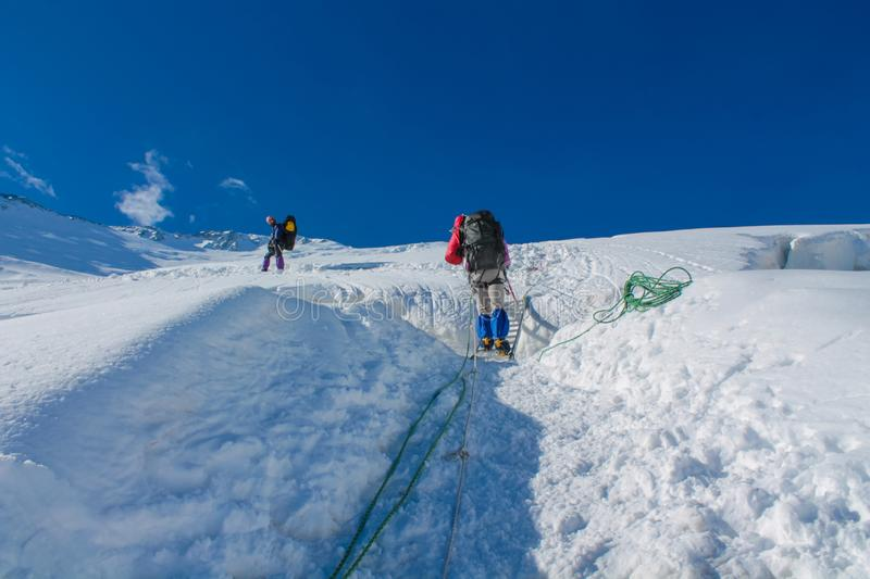 Mountaineers on the  snow of mountain glacier in Himalaya summit ascent. Mountaineers on snow of mountain glacier, climbing alpinist route. Alpinist with stock images
