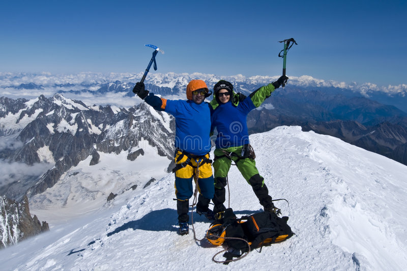 Mountaineers on top of alps - succes stock photography