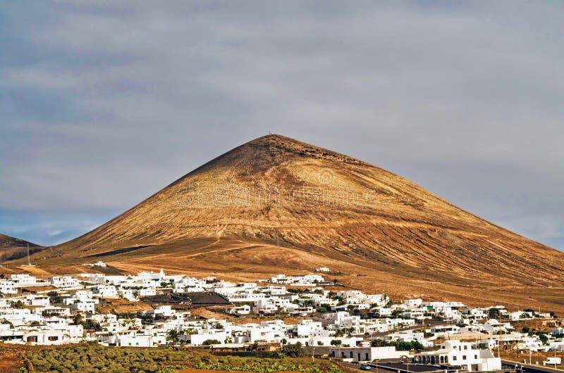 Mountainous Landforms of Lanzarote. Buildings in the municipality of Tias against cloudy sky. Photo taken on Lanzarote, Las Palmas, Spain royalty free stock photos