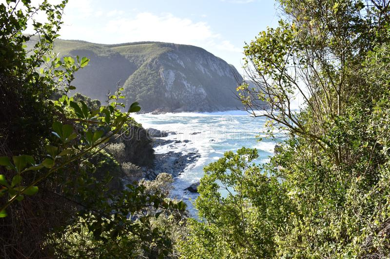 Mountainous Landscape with the beautiful beach and the famous Storms River Bridge at Tsitsikamma National Park in South Africa stock photo