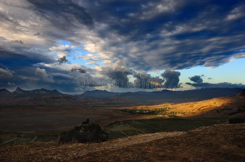 The mountainous landscape in the early morning. The brightly expressed clouds above the mountain valley with the village royalty free stock photography