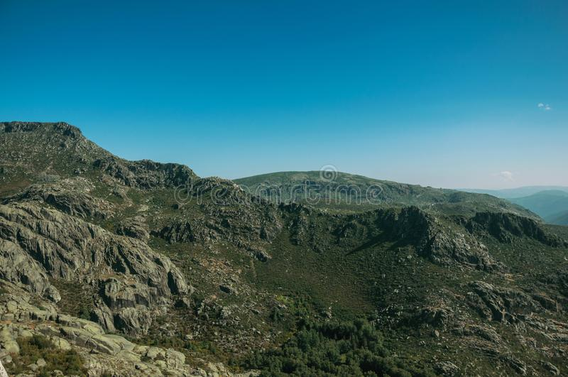 Mountainous landscape with rocky cliffs. Covered by green bushes in a sunny day, at the highlands of Serra da Estrela. The highest mountain range in continental royalty free stock photos