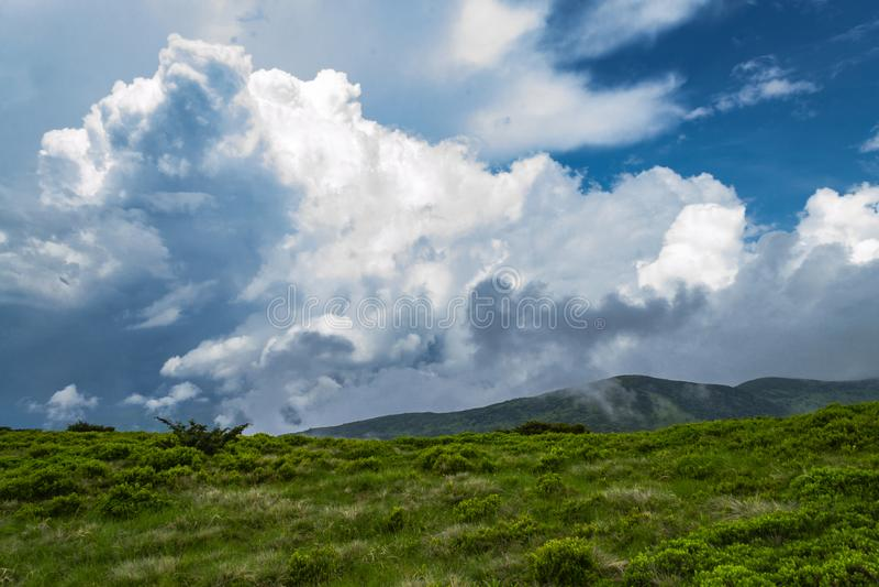 Mountainpeakll med grönt gräs och blå himmel Fantastiskt skott royaltyfri fotografi