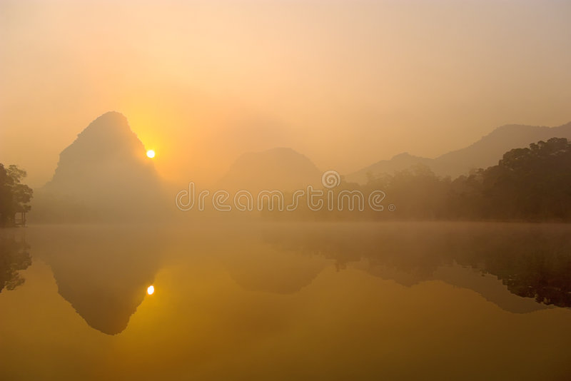 Mountains. Morning mist over the lake, the sun rose up from the mountain royalty free stock images