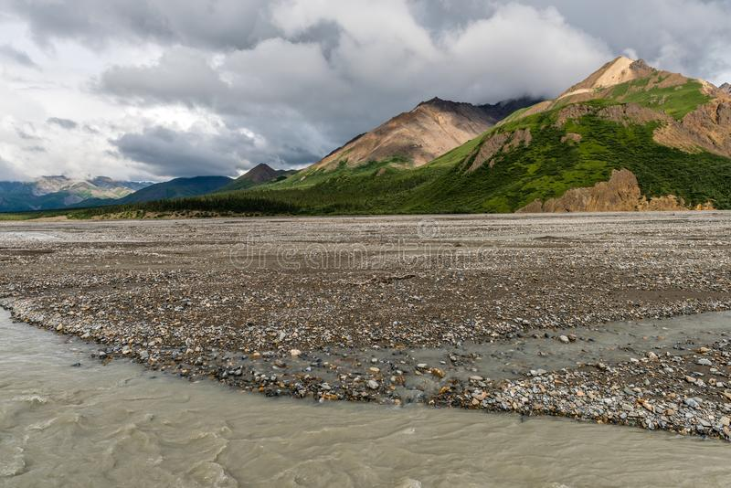 Mountains Tower Over a Gravel Flat in Alaska`s Denali National Park royalty free stock photo