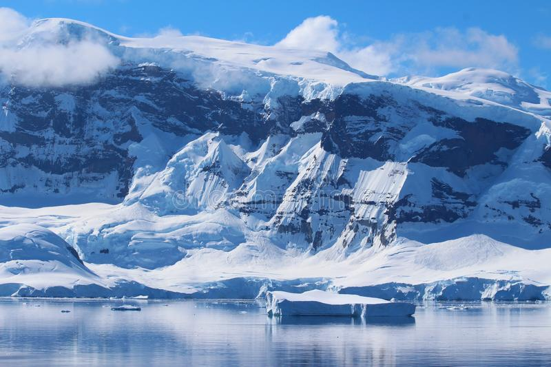 Mountains along the Antarctic Peninsula, Antarctica. View of mountains, clouds and icebergs in Antarctica. Antarctica along the Antarctic Peninsula royalty free stock photo