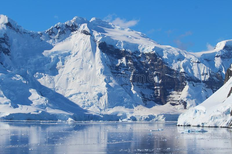 Mountains along the Antarctic Peninsula, Antarctica. View of mountains, clouds and icebergs in Antarctica. Antarctica along the Antarctic Peninsula royalty free stock image