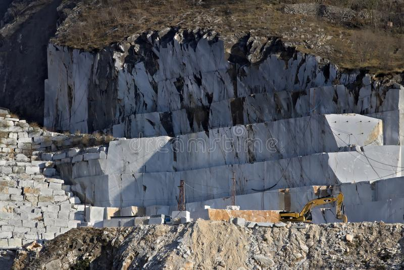 Apuan Alps, Carrara, Tuscany, Italy. March 28, 2019.  An excavator in a quarry of white Carrara marble royalty free stock photos