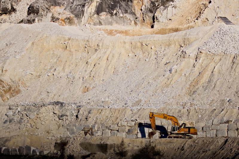 Apuan Alps, Carrara, Tuscany, Italy. March 28, 2019.  An excavator in a quarry of white Carrara marble royalty free stock image