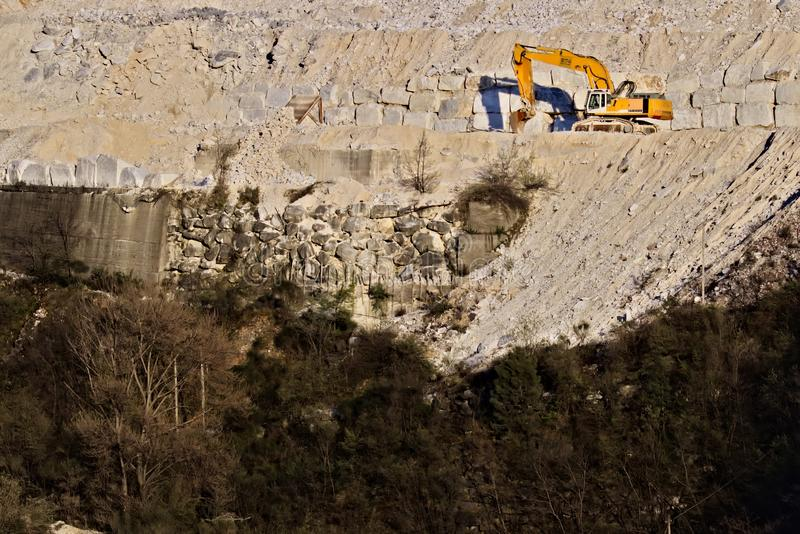 Apuan Alps, Carrara, Tuscany, Italy. March 28, 2019.  An excavator in a quarry of white Carrara marble royalty free stock images