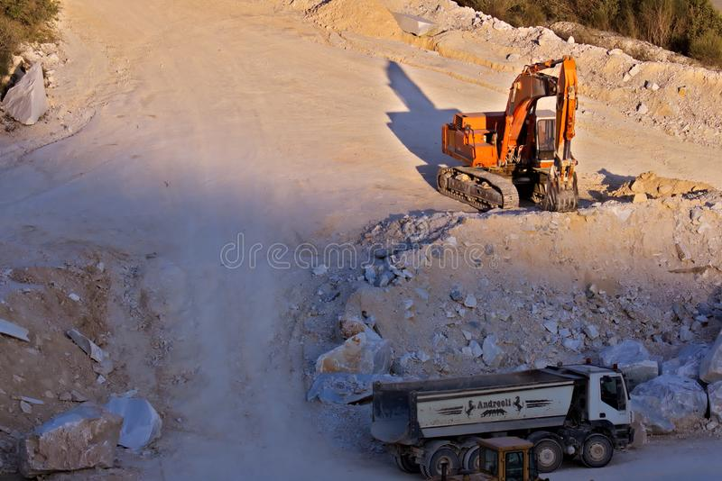 Apuan Alps, Carrara, Tuscany, Italy. March 28, 2019.  An excavator in a quarry of white Carrara marble stock photo