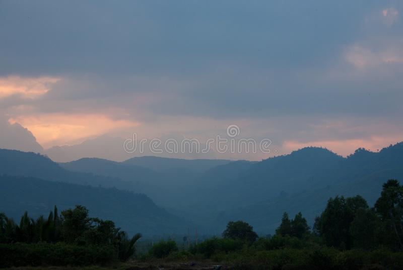 Mountains during a beautiful sunset near Kampot in Cambodia. In Asia, adventure, asian, boat, calm, chhu, chill, cloud, color, cruise, dark, destination, dusk stock image