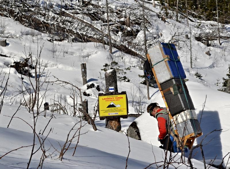 Mountains carrier with a heavy load takes goods to a chalet stock images