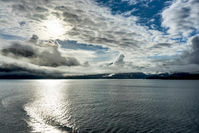 Mountains covered in clouds on a misty morning on the Ferry towa. Photo taken in Alaska, United States of America royalty free stock images