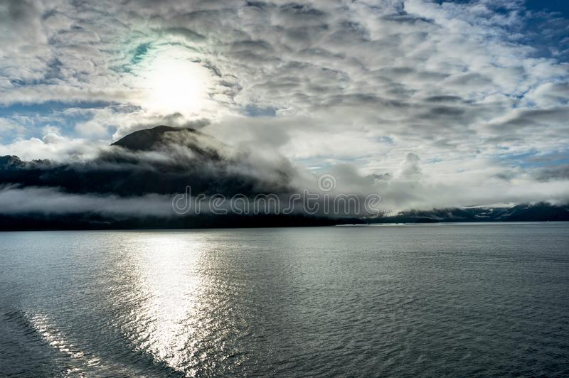 Mountains covered in clouds on a misty morning on the Ferry towa. Photo taken in Alaska, United States of America stock image