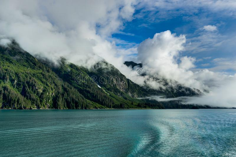 Mountains covered in clouds on a misty morning on the Ferry towa. Photo taken in Alaska, United States of America royalty free stock photography