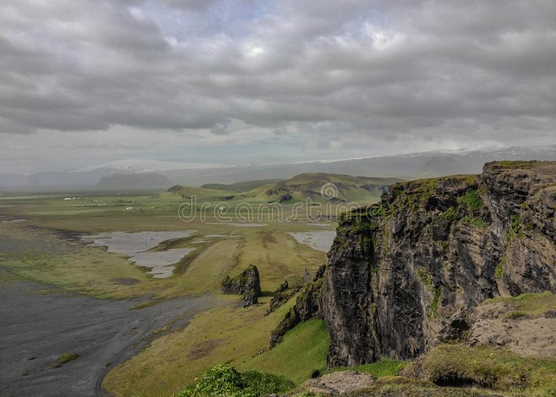 Mountains covered with green moss, black sand beach and white ocean waves on the background. Dyrholaey, South Iceland, Europe. Epic landscape of Dyrholaey royalty free stock photography