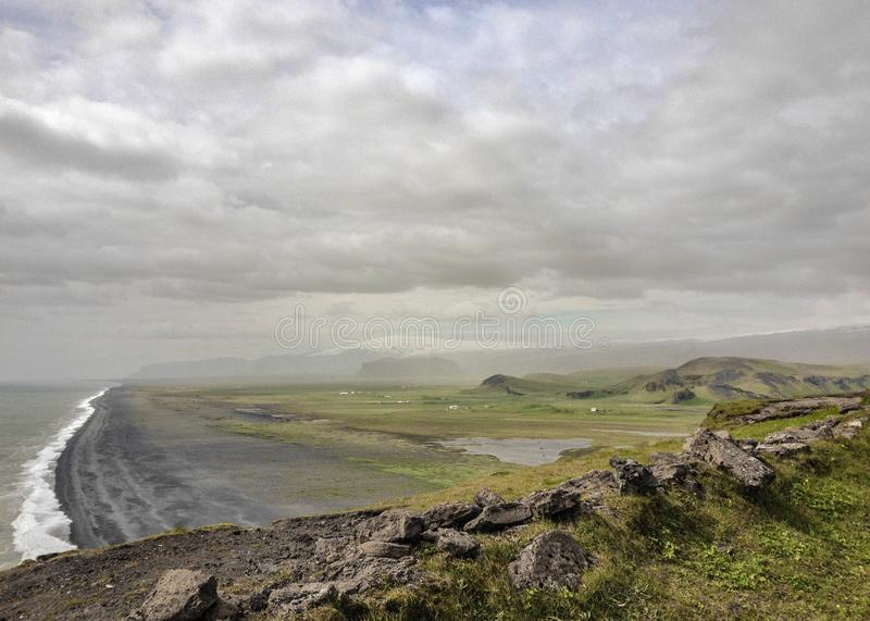 Mountains covered with green moss, black sand beach and white ocean waves on the background. Dyrholaey, South Iceland, Europe. Epic landscape of Dyrholaey stock photo