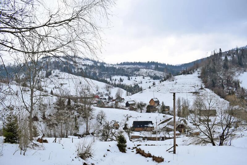 Mountains covered with snow against a gray sky. Winter landscape in a village in the mountains. Several wooden houses located on the hills royalty free stock photo
