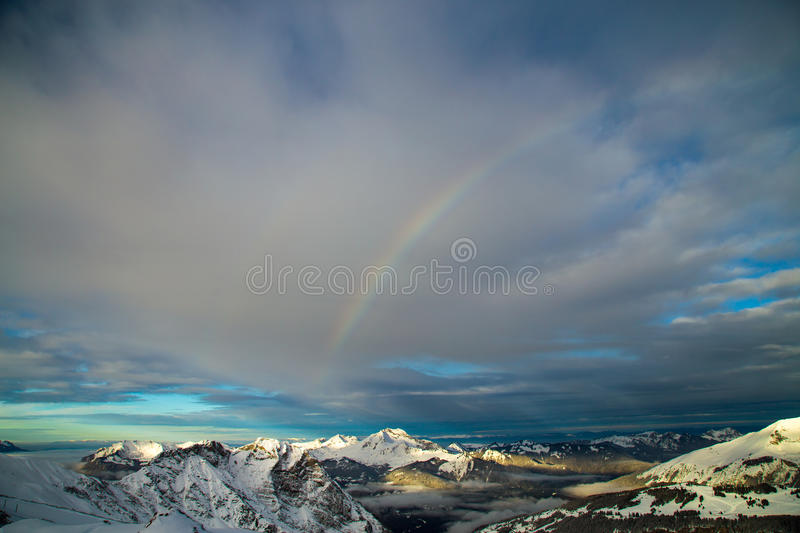 Mountains covered with snow and surrounded by clouds stock photos