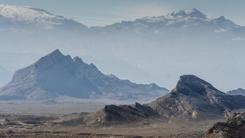 Mountains in desert. Photography of sharp mountains rising from Dasht-e Lut desert in Yazd province, Iran royalty free stock photo