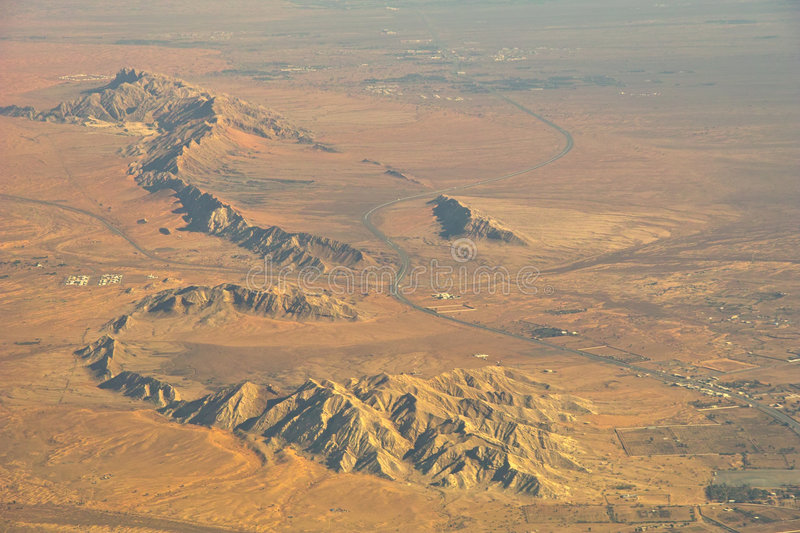 Mountains, desert, settlement. Morning. The view on the mountains in the middle east desert from airplane. The single houses of the small settlement with royalty free stock photos