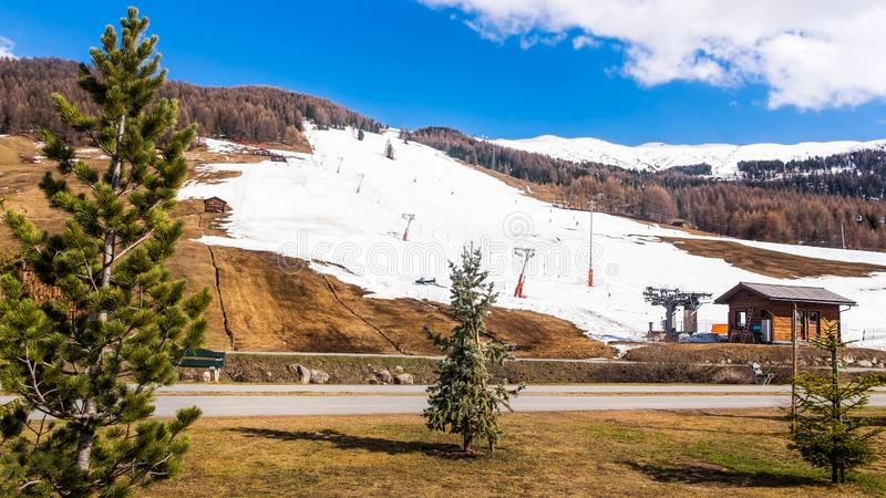 Mountains in early spring, slopes and pistes with ski lifts, Livigno village, Italy, Alps. Beautiful mountains in early spring, slopes and pistes with ski lifts stock image