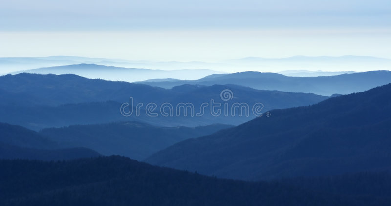 Mountains in the fog. View of far away blue mountains in the fog stock images