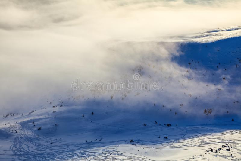 Mountains in fog. Morning lights. Fantastic winter scenery. Texturally frozen snow. Frozen snowflakes. stock photography