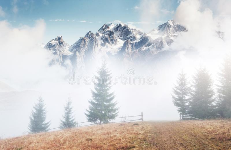 Mountains in fog. Peaks under heavy clouds. Silent autumn landscape. Snow on hills.  stock images
