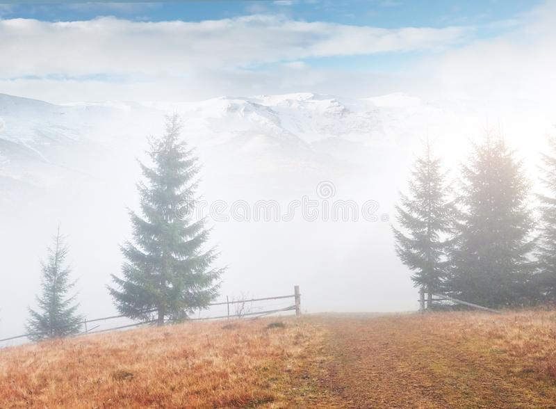 Mountains in fog. Peaks under heavy clouds. Silent autumn landscape. Snow on hills.  royalty free stock photo