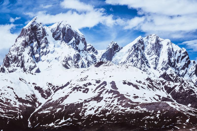 Mountains in Georgia covered with snow. Including a horned peak called Ushba Mountain, 4690 m. Against blue sky with beautiful clouds. View from ski resort royalty free stock photo
