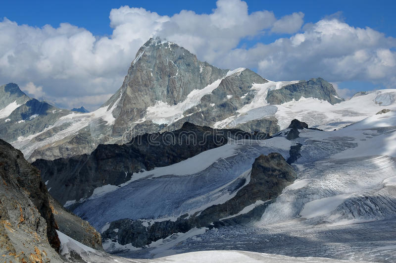 Mountains and glaciers. The high summit of the Dent Blanche a challlenging peak to climb in Switzerland surrounded by glaciers and blue ice. Viewed from the west stock photos
