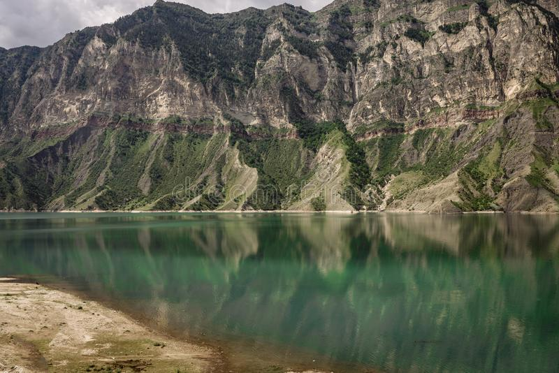 Mountains and lake against a cloudy sky. Gunib district of Dagestan. Mountains and transparent lake against a cloudy sky. Gunib district of Dagestan royalty free stock photography