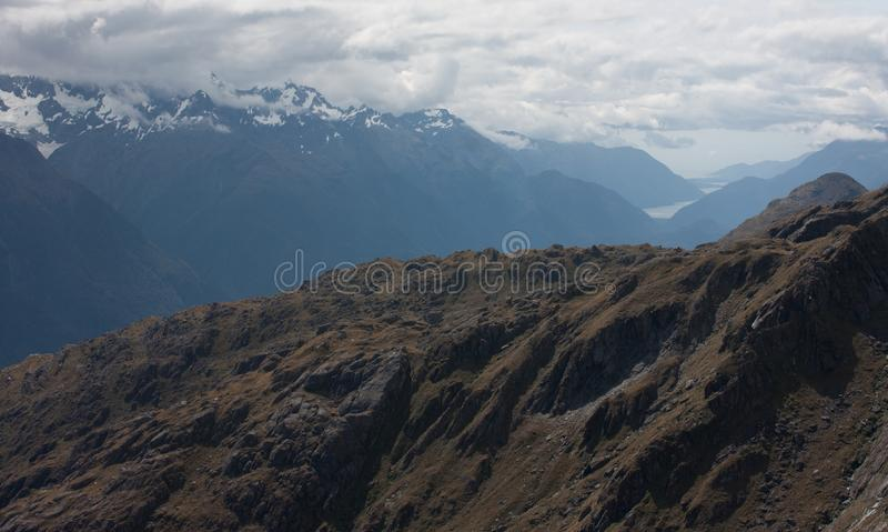 Mountains, Lake Mckerrow and Tasman Sea in the distance as seen from the top of the Conical Hill at Harris Saddle at the Routeburn. Great walk in Fiordland, New royalty free stock photography