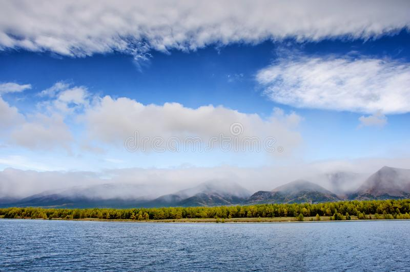 Mountains landscape - cloudy sky in pastel colors for your design. Romantic seascape - seaside view with silhouettes of. Blue hills in a fog and fall forest stock images