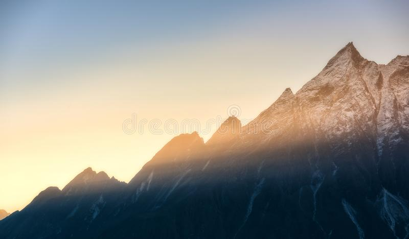 Mountains and low clouds at colorful sunrise in Nepal royalty free stock photo