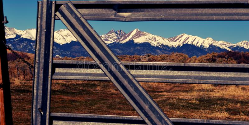 Mountains and Metal. Sangre de Cristo Mountains framed in a ranch metal fence stock images