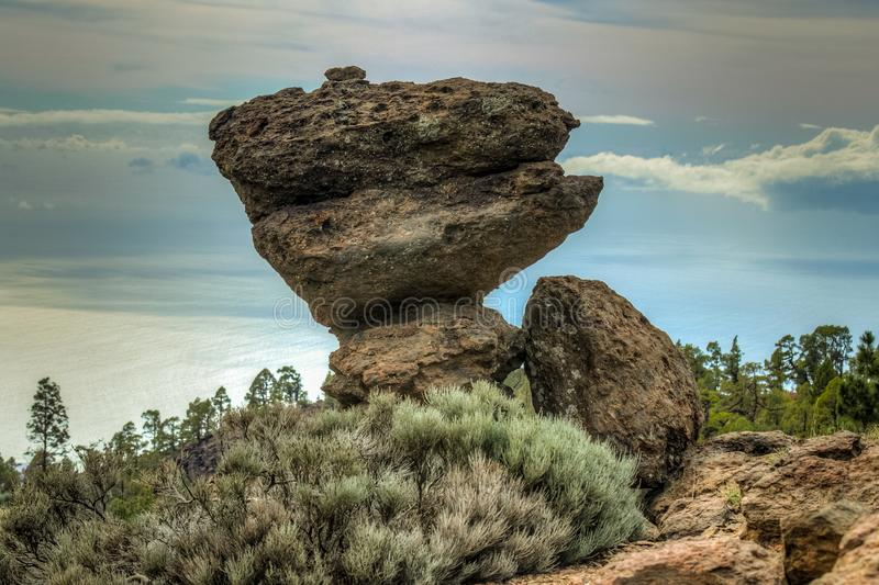 Mountains near Teide National Park. Old pine forest. The game of nature. A huge volcanic boulder on a small stone seems to be royalty free stock photo