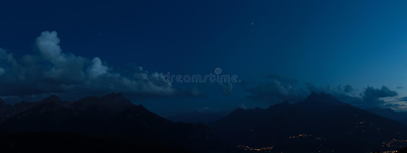 Mountains At Night. Nocturnal alpine landscape with mountains and clouds stock photos