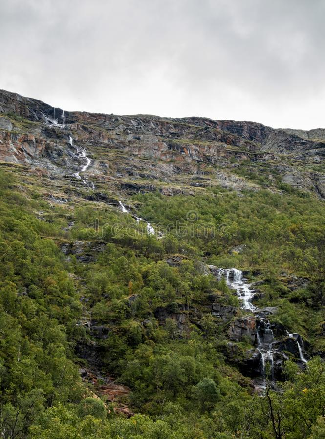 Mountains Norway waterfall river down the hill with cloudy sky. Wild nature northern autumn landscape royalty free stock photo