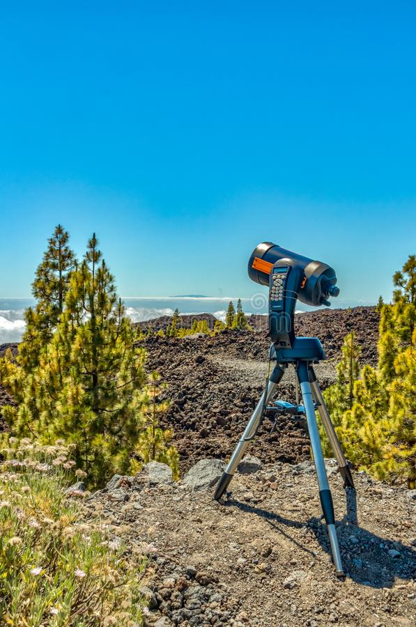 Mountains and pine tree forest near volcano Teide, partly covered by the clouds. Bright blue sky. Telescope on the tripod ready stock images