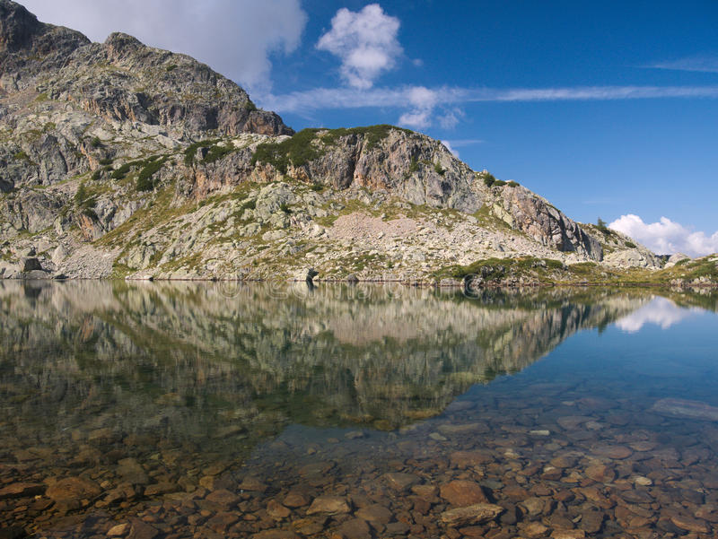 Mountains reflect on small alpine lake on the Bergamo Alps stock photography