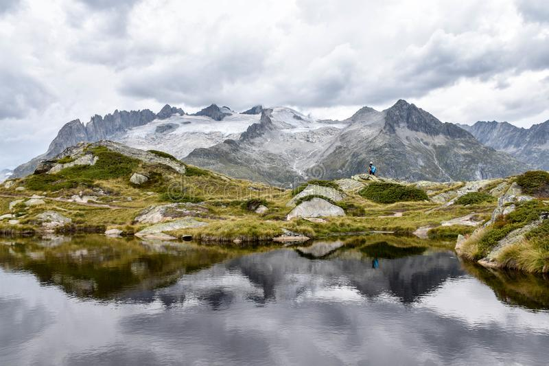 Mountains reflected in a rippled lake in the Swiss Alps, with a. View to a glacier, and a lone traveller hiking stock image