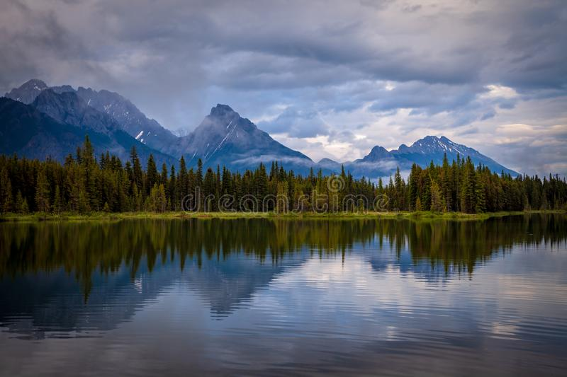Mountains reflecting in the calm waters of Spillway Lake in Peter Lougheed Provincial Park, Alberta stock image