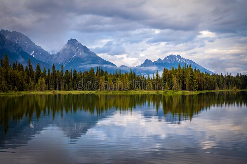 Mountains reflecting in the calm waters of Spillway Lake in Peter Lougheed Provincial Park, Alberta royalty free stock image